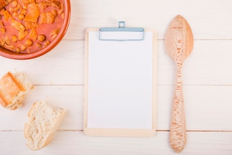 Clipboard with spoon and dish on table