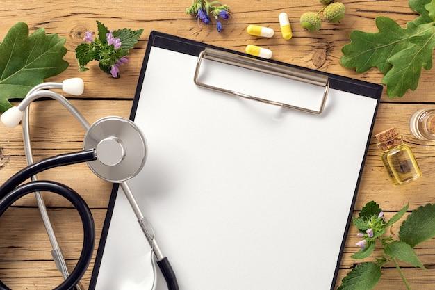 聴診器、さまざまな植物、癒しのハーブの葉、カプセル、健康的なオイルを使用したクリップボード