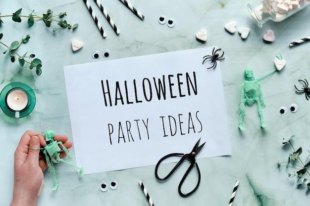 ミントグリーンの背景にテキストハロウィーンパーティーのアイデアとクリップボード。スケルトンを手にフラットレイ、