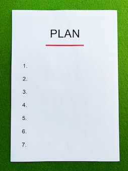 Clipboard with text plan on green desk.