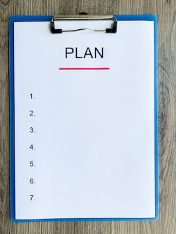 Clipboard with text plan on wood desk.