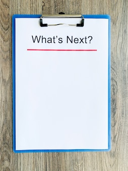 Clipboard with text what's next on wood desk.