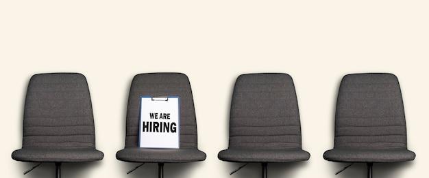 우리가 고용하는 비문 클립 보드는 흰색에 회색 사무실 의자에 놓여 있습니다.