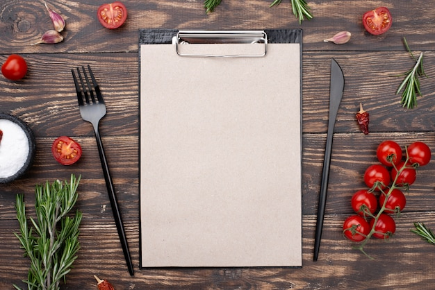 Clipboard with tomatoes and cutlery on table