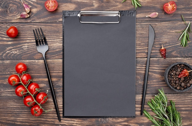 Clipboard with tomatoes and cutlery