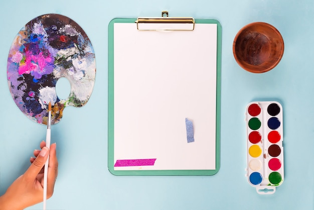 Clipboard with watercolor paints in box, in the hands of brushes and palette on blue
