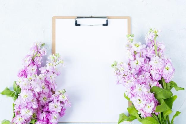 Буфер обмена с белым чистым листом бумаги и цветами на белом фоне.