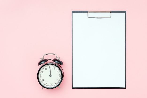 Clipboard with white blank paper and black alarm clock on pink background. empty card for to-do list, schedule, plan and other text