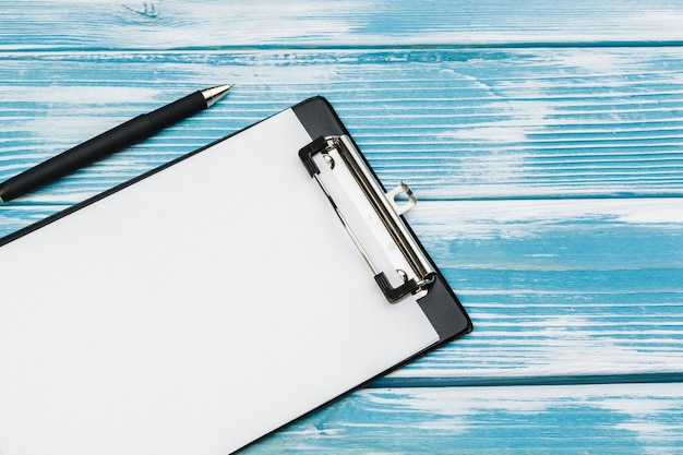 Clipboard with white blank paper on blue wooden surface table, top view