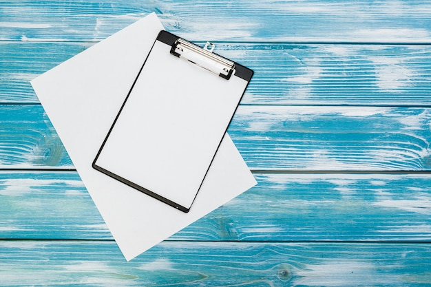 Clipboard with white blank paper on blue wooden table