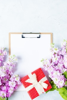 Clipboard with white blank paper, present gift box and flowers on white background.