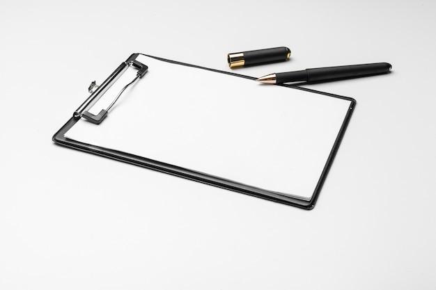 Доска сзажимом для бумаги с белым листом и ручка изолированная на белизне.
