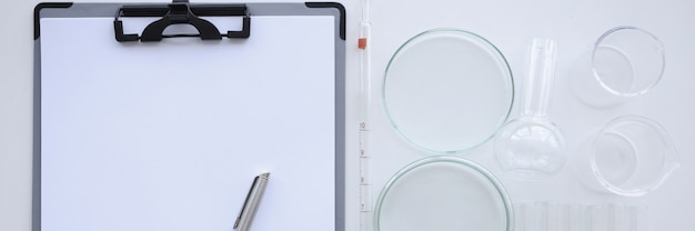 흰색 시트와 펜 클립 보드는 플라스크 및 화학 테스트 튜브 옆 테이블에 놓여 있습니다.