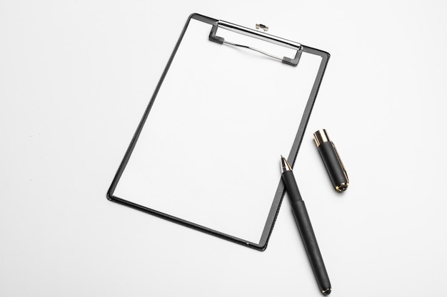 Clipboard with white sheet and pen isolated. top view