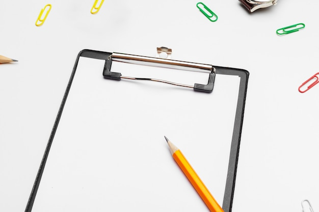 Clipboard with white sheet and pen isolated on a white . top view