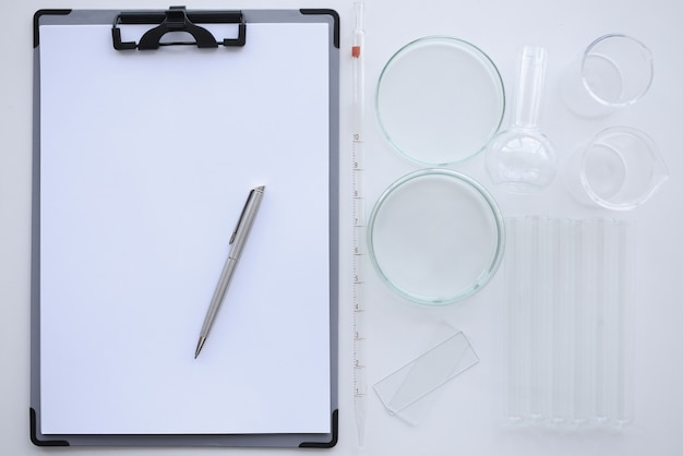 Clipboard with white sheet and pen lies on table next petri dishes