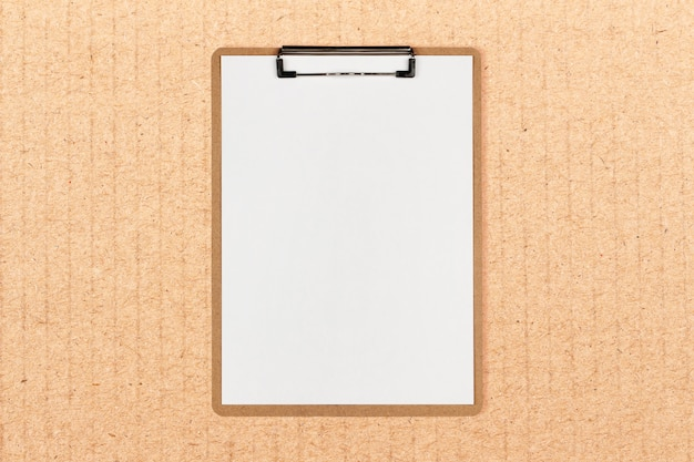 Clipboard with white sheet and space for text on craft paper background