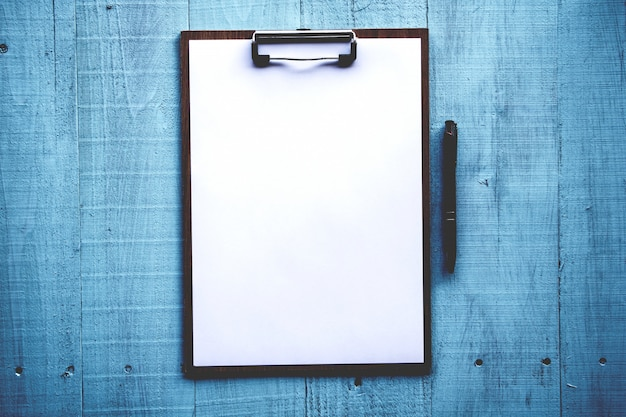 Clipboard with white sheet on wood background