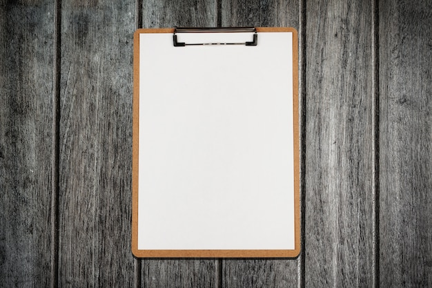 Clipboard with white sheet on wooden background Premium Photo