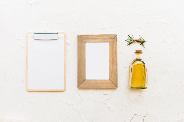 Clipboard and wooden frame with oil bottle and rosemary herb
