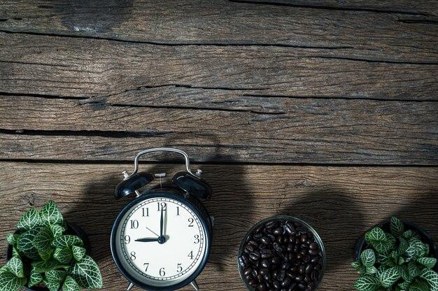 Часы и кружка кофейных зерен, размещенные на столе, вид