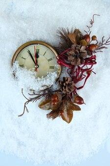 Часы и рождественские украшения под снегом крупным планом