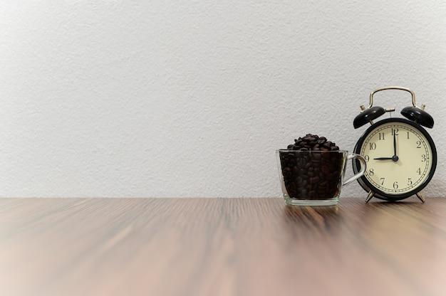 Часы и кофейные зерна поставлены на стол