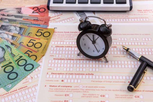 オーストラリアの税務フォームの時計とペンをクローズアップ