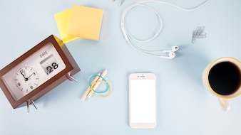 Clock and school supplies near smartphone and drink