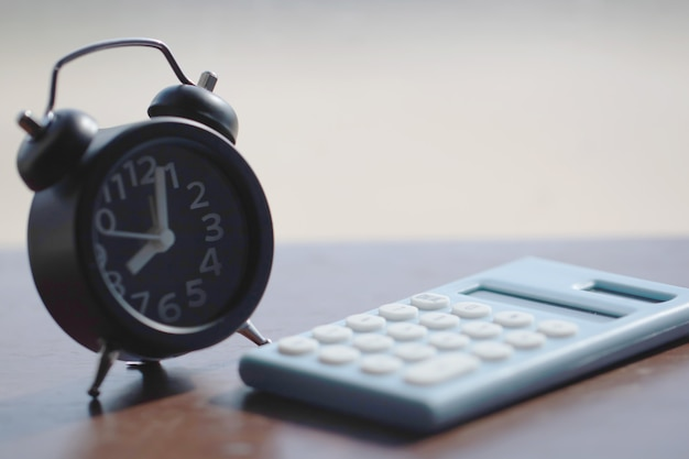 Clock and calculator on wood background for finance