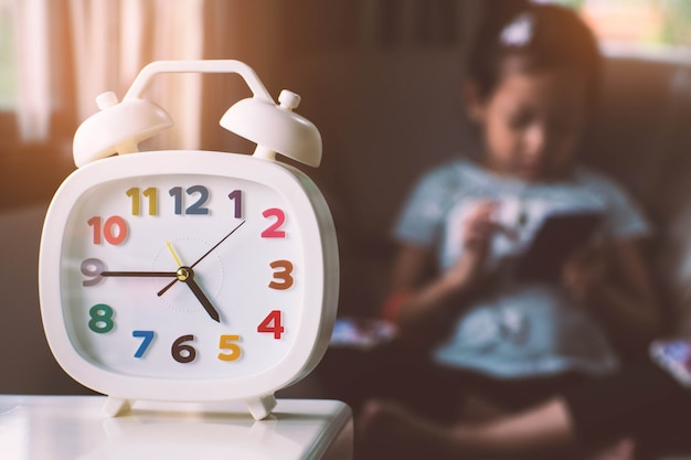 Clock and child playing smartphone.