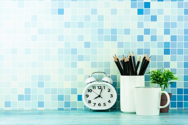 Clock, coffee cup, and a pencil on blue wooden desk