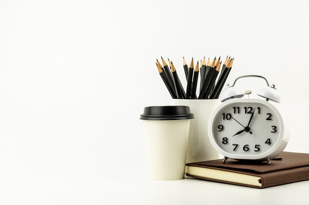 Clock, coffee cup, pencil, and a leather notebook on white desk background with copy space. - office supplies or education concept.