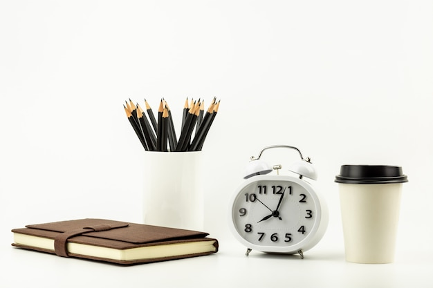 Clock, coffee cup, pencil, and a leather notebook on white desk background with copy space