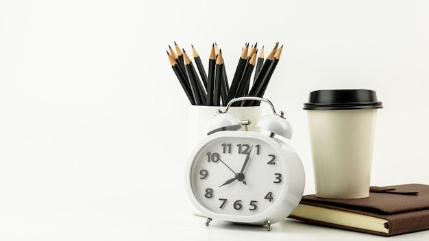 Clock, coffee cup, pencil, and a leather notebook on white desk background with copy space.