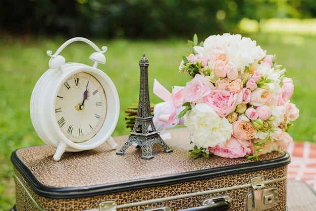 Clock, eiffel tower and bouquet on a retro suitcase