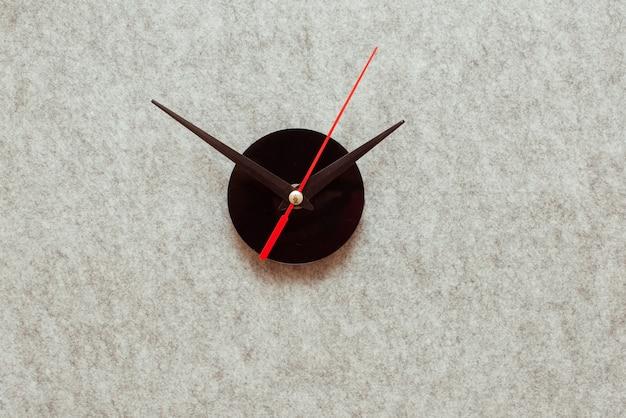灰色の背景に時計の針。最小限の時間の概念