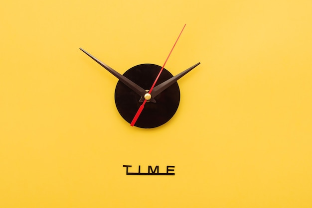 Clock hands on yellow background. minimal time concept