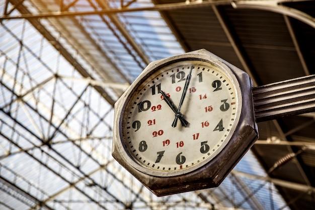 기차역의 시계, 큰 오래된 빈티지 시계가 기차역의 지붕과 함께 걸어