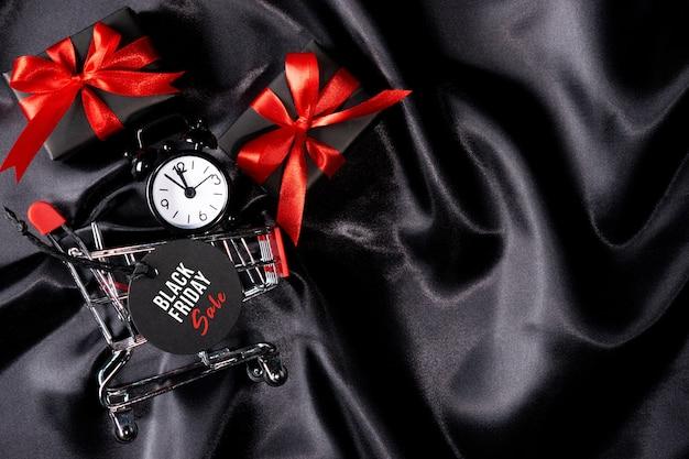 Часы в корзине с черной биркой и подарками на черной ткани.