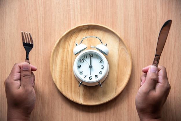 The clock is at 12:00 noon for lunch in a wooden dish.