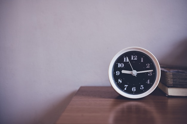 The clock is on table in bedroom