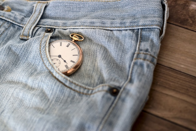 Clock in a jeans pocket on a wooden surface - time management concept