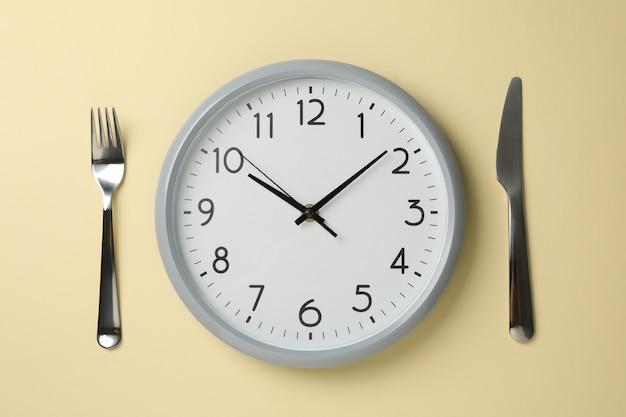 베이지 색 배경, 평면도에 시계, 나이프와 포크