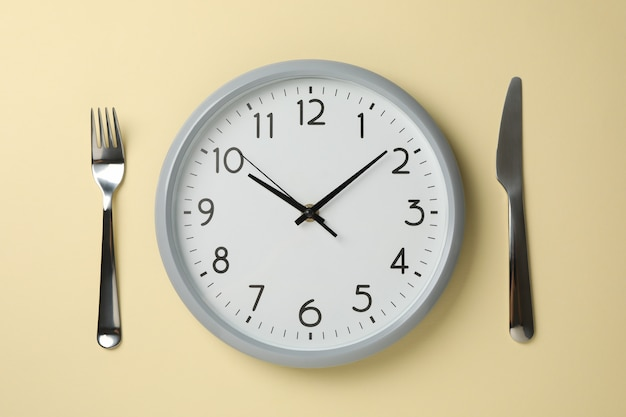 Clock, knife and fork on beige background, top view