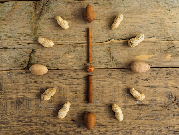 Clock made of different nuts and cinnamon on wooden table