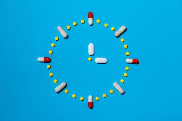처방에 따라 제 시간에 약을 복용한다는 개념으로 다채로운 알약으로 만든 시계. 마약 중독, 진통제 캡슐.