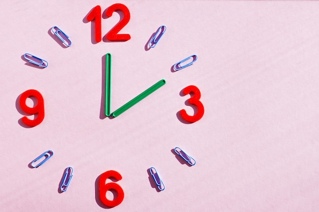 A clock made of numbers, paper clips, and sticks from a children learning kit.