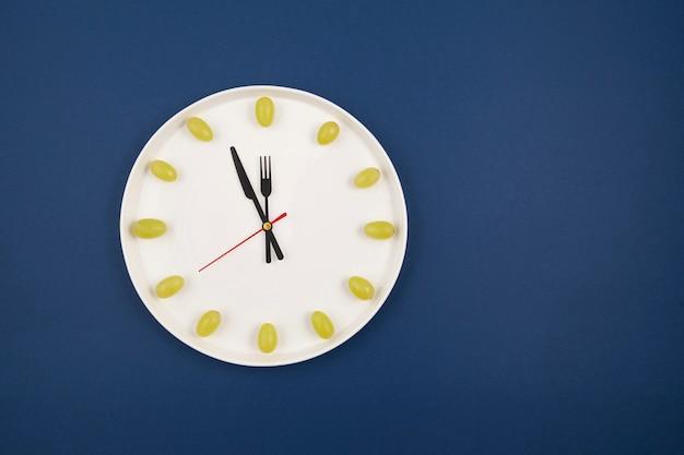 Часы из винограда на синем