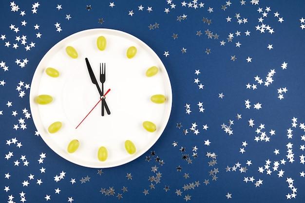 ブドウで作られた時計スペインの新年の伝統で、深夜に幸運を祈って12個のブドウを12個食べる